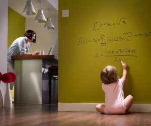 Successful baby doing algebra on hallway wall