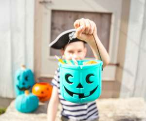 kid holding teal pumpkin filled with allergy free candy