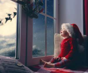 "baby looking out at window wondering ""is santa is real?"""