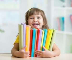 Smiling Kindergarten Girl Holding Stack of Books