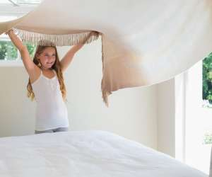 Young girl making her bed with her mom