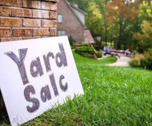 Handmade yard sale sign leaning on brick wall